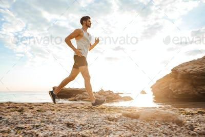 Handsome man athlete running at the beach
