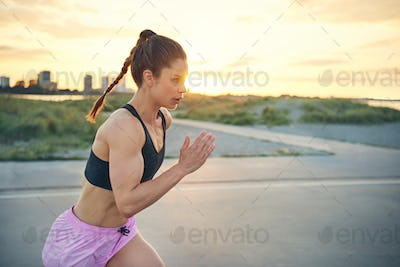 Fit young woman practising her sprinting technique