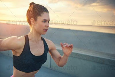 Young woman out running at sunrise