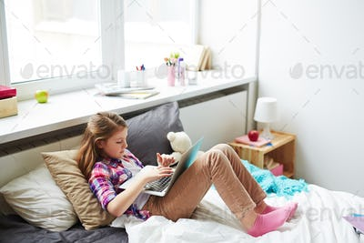 Teenager Girl on Bed with Laptop