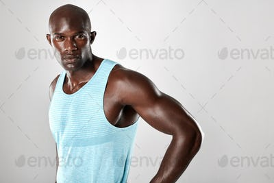 Fit young man with muscular build standing against grey backgrou