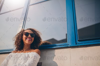 Smiling young african woman sitting outdoors