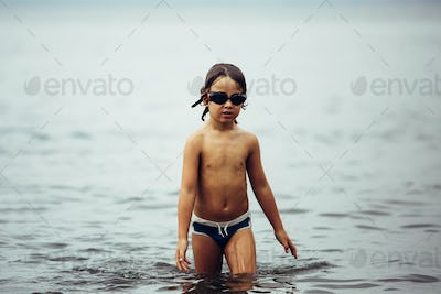 Wet-haired kid in goggles walking in sea
