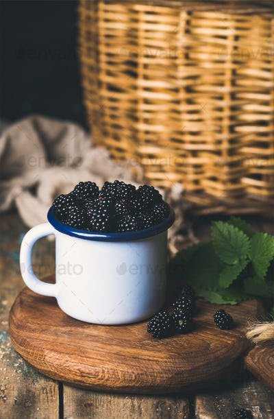 Fresh Blackberries in white cup on round serving wooden