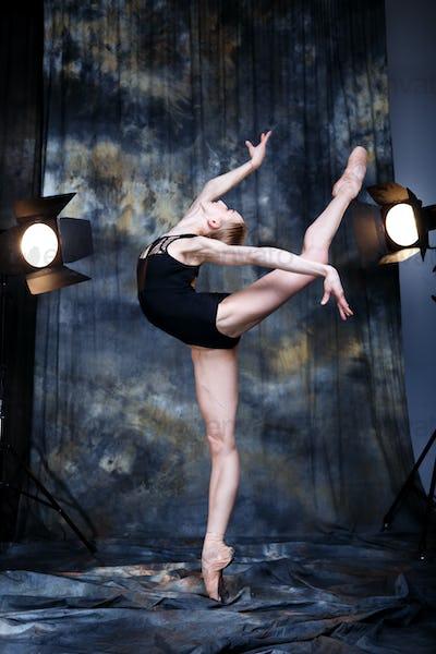 Young ballerina in a dark studio
