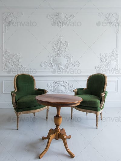 Luxury clean bright white interior with a old antique vintage green chairs over wall design bas