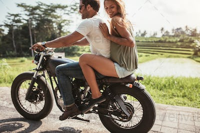 Young couple riding on a motorbike