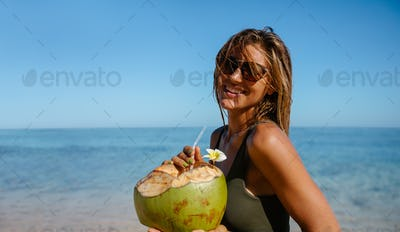 Beautiful woman with fresh coconut on the beach