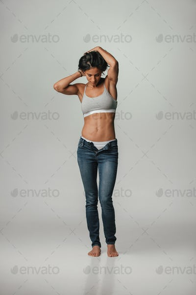 Trendy young woman posing in underwear and jeans