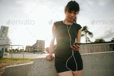 Caucasian woman having a break after running outdoors