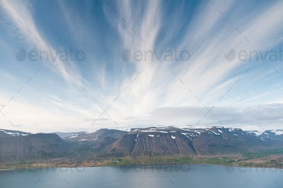 fjord surrounded by beautiful mountgains bathing in evening light