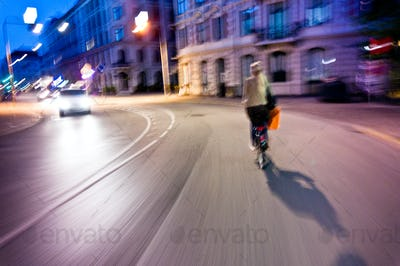 woman rides bicycle in the night - genuine motion blur and vibrant colors