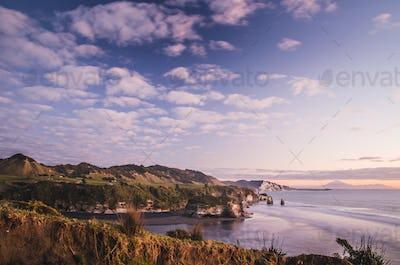sunset over sea shore rocks and mount Taranaki, New Zealand