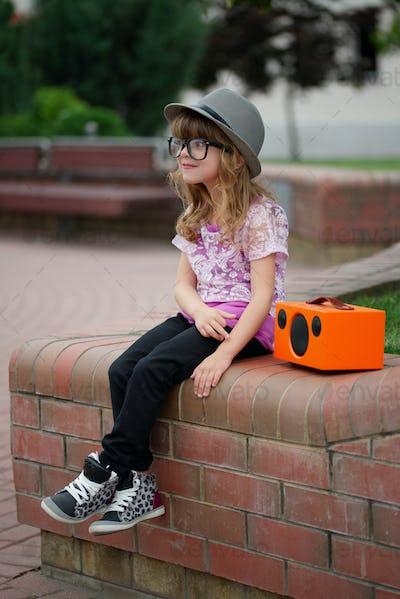 hipster girl listens music on wireless retro looking speaker