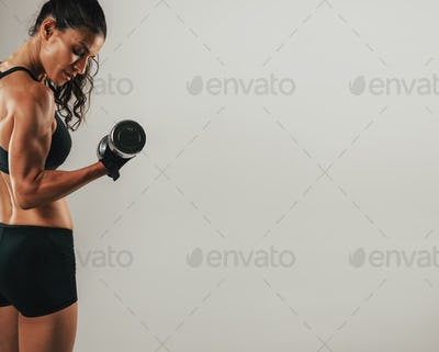 Fit young woman working out with a dumbbell