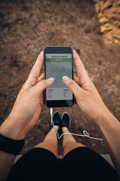 Female runner using a fitness app on her mobile phone