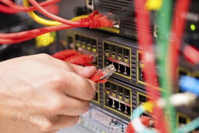 IT consultant connects a network cable into switch in datacenter