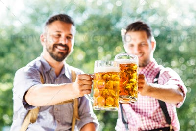 Men in traditional bavarian clothes holding mugs of beer
