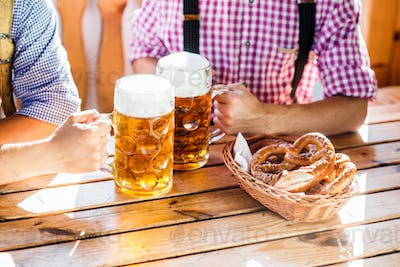 Man in traditional bavarian clothes holding mugs of beer