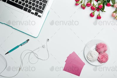 Office desk table with computer, supplies, flowers