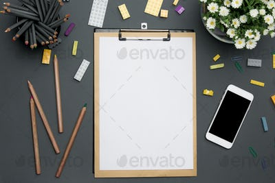 Office desk table with pencils, supplies, phone and flowers