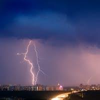 Lightning strike over city in purple light.