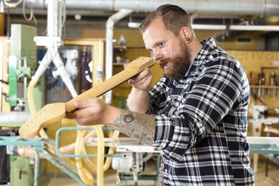 Carpenter inspects a wooden guitar neck in workshop
