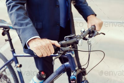 Successful businessman riding bicycle