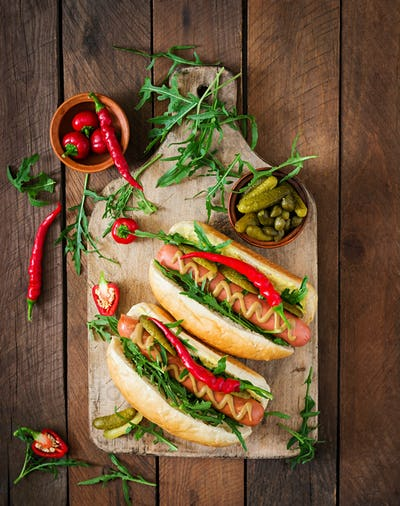 Hot dog with pickles, capers and arugula on wooden background. Top view