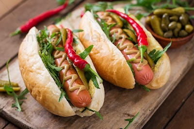 Hot dog with pickles, capers and arugula on wooden background.