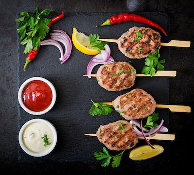 Appetizing kofta kebab (meatballs) with sauce on black background. Top view