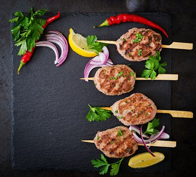 Appetizing kofta kebab (meatballs) on black background. Top view