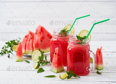 Fresh watermelon smoothies with lime and mint on white wooden background