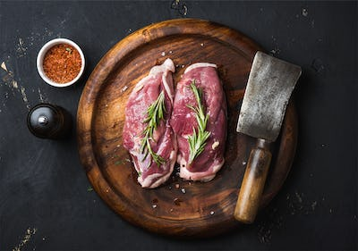 Raw duck breast with rosemary, spices on dark wooden tray