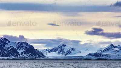 Clouds over snowy mountains and glacier in the arctic