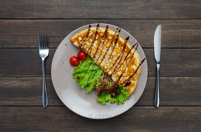 Restaurant food top view on wooden table. Omelette with vegetables
