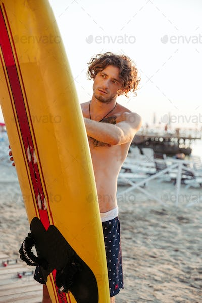 Professional young surfer getting board ready for surf