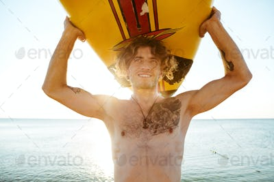 Close up face of handsome guy with surfboard on head