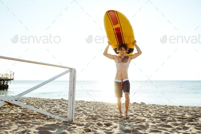 Handsome surfer carrying his surfboard across beach in evening sunlight
