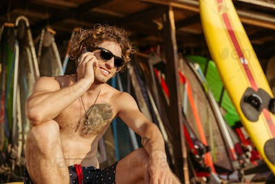Close up portrait of a surfer man talking on smartphone