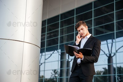Businessman in suit holding folders and talking on the phone