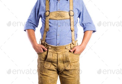 Unrecognizable man in traditional bavarian clothes, hands in poc