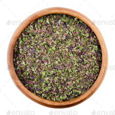 Seaweed flakes in a bowl over white