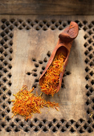 Saffron spice threads in scoop on carved tray