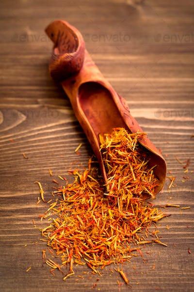 Saffron spice threads in scoop on wooden background