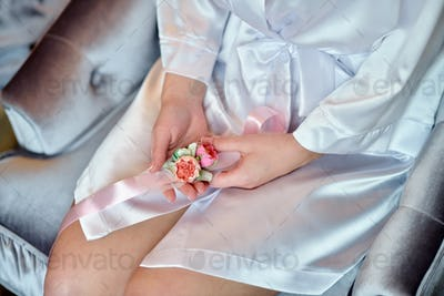 Hands of beautiful bride in white dressing gown