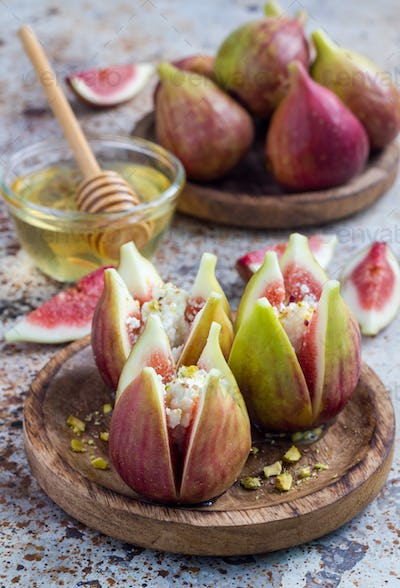 Figs, cheese, pistachio and honey dessert on wooden plate, vertical