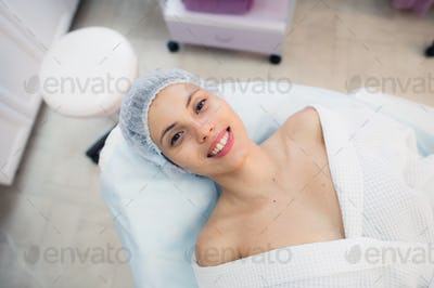 Top view of beautiful young woman getting ready for face skin treatment, lying on bed at hospital or