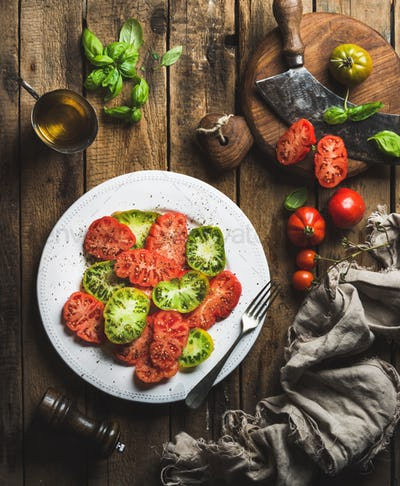 Tomato salad with olive oil and basil over wooden background
