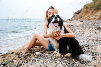 Happy woman hugging her dog on the beach